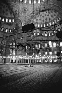 Muslim believer praying inside a mosque, black and white photo, grain film added.