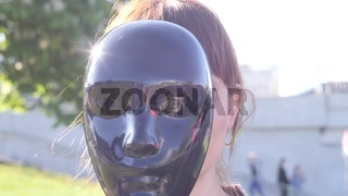 portrait of a young pretty charismatic woman who hiding her face behind the black mask and then sets it aside and smiles against the background of the city, close up video in slow motion in 4K