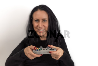 Young woman with red nail polish  playing video game on a retro wireless gaming controller with a happy and concentrated facial expressions isolated on white background