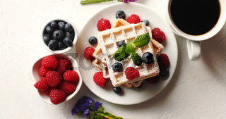 Coffee and berries near waffles