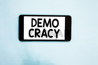Text sign showing Demo Cracy. Conceptual photo freedom of the people to express their feelings and beliefs Cell phone white screen over light blue background text messages apps.