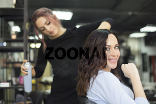Young female hairdresser fixing hair of gorgeous woman with hairspray