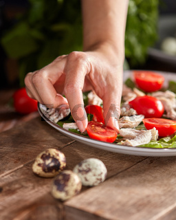 Woman hand put tomato cherry to a ceramic plate of fresh salad with organic ingredients on a wooden table. Healthy diet food.