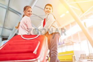 Kinder mit Koffer am Flughafen vor Abreise