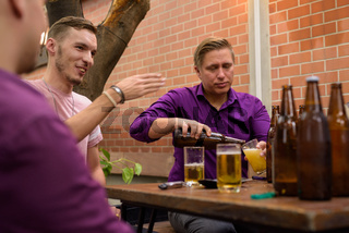 Man filling glass with beer while friends are talking and sitting