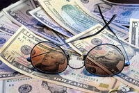 Sunglasses is placed on the banknote of US dollars spread around