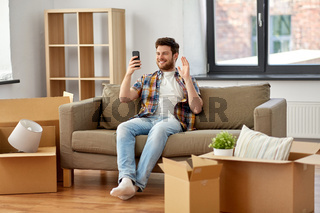 man with smartphone having video call at new home