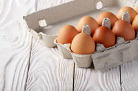 Raw organic brown chicken eggs in eco friendly paper carton on white kitchen wooden table