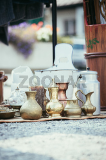 Antique teapots, creamer and other utensils at a flea market. Old metal tableware at a garage sale.