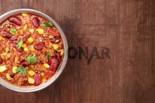 Chili con carne, a Mexican stew with red beans, cilantro leaves, ground beef, and chili peppers, close-up overhead shot on a dark rustic wooden background with copy space