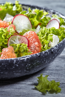Delicious natural vegetarian salad with fresly picked vegetables, lettuce, citrus fruit, cheese in a gray plate on a gray wooden background.