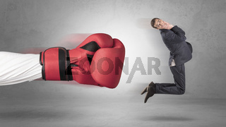 Businessman gets a hit from a giant hand