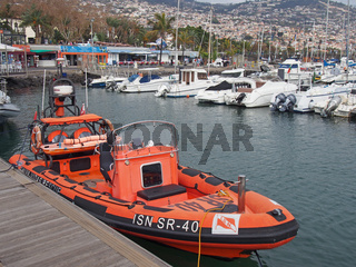 an orange rescue boat belonging to the Portuguese lsn national lifeboat service moored in the marina with yachts and waterside cafes in the background