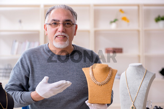 White bearded old jeweler at workshop