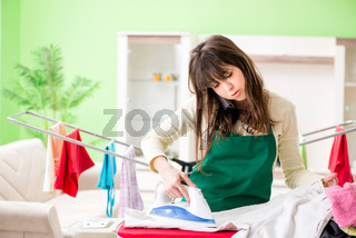 The young woman ironing clothing at home