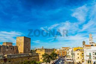Bari, Italy - March 10, 2019: View of the Svevo castle and the square of Federico II di Svevia a spring day with a background of blue sky and clouds.