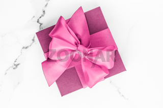 Pink gift box with silk bow on marble background, girl baby shower present and glamour fashion gift for luxury beauty brand, holiday flatlay art design