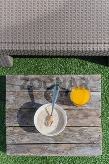 Outdoors breakfast with orange juice and a bowl of cereals and milk