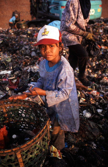Jakarta, Indonesia, A young girl searches for recyclable materials at the Bantar Gebang landfill