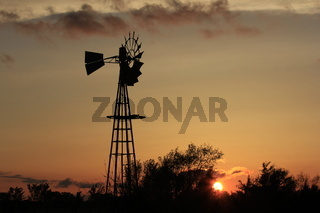 Kansas Sunset with Windmill and Tree Silhouettes with clouds
