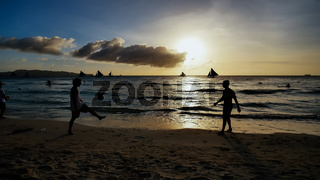 Beach on the island of Boracay in the rays of the evening sunset. Silhouettes of people playing a ball on the beach and sailboats on the water.