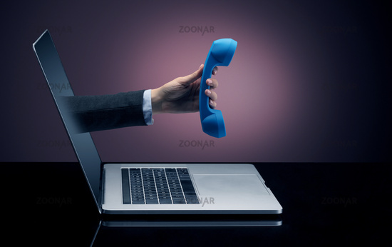 Hand with phone coming out of a laptop