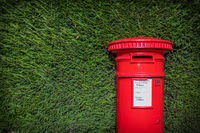 Classic Red British Pillar Box Against Hedge