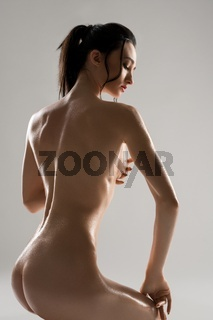 Slim brunette in the nude rearview