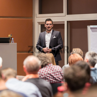 Business speaker giving a talk at conference meeting.
