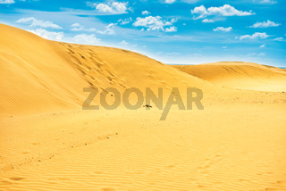 Desert with sand dunes and clouds on blue sky