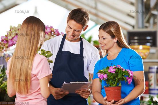 Mitarbeiter im Blumenladen bei Beratung von Kunden
