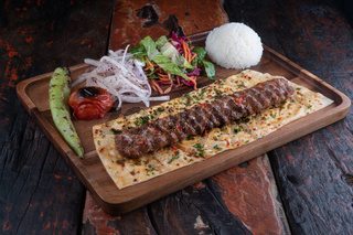 Turkish lula lamb or beef kebab with rice and vegetables on rustic wooden table