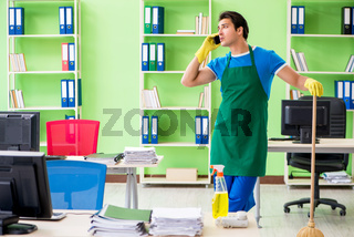 Young male handsome professional cleaner cleaning floor with bro