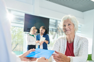 Positive senior lady receiving envelope with documents in bank