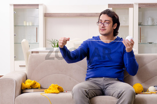 Young good looking man knitting at home