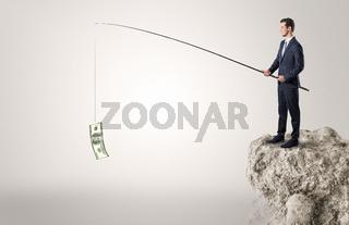 Businessman fishing dollar from a rock