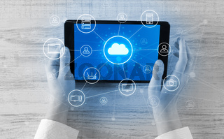Hand using tablet with centralized cloud computing system concept