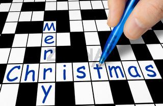 Hand filling in crossword - Merry Christmas