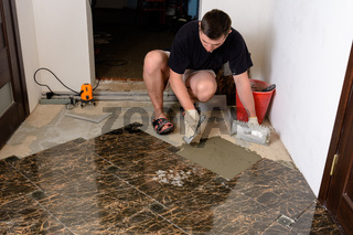 Master husband presses a spatula glutinous solution to the cement surface