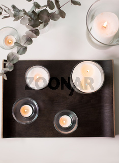 candles and branches of eucalyptus on table