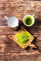 Matcha tea with powdered green tea and milk jug on a dark rustic wooden board.