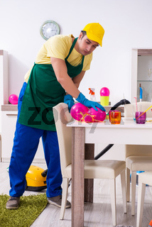 Young male contractor doing housework after party