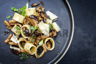 Traditional Italien calamarata noodles with mushroom and parmesan as top view on a plate with copy space right
