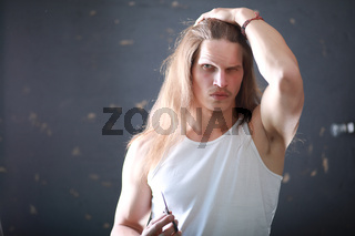 A young man with long hair cut a lock