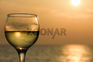 Glass Filled With White Wine Against Sea At Sunset
