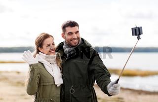 happy couple taking selfie on beach in autumn