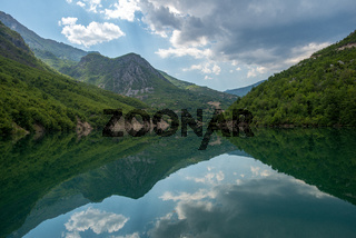 Mountains reflecting in Komani Lake, Albania