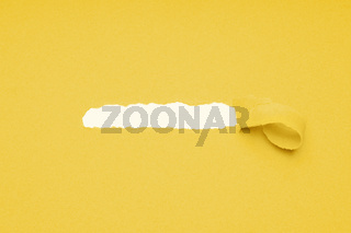 hole ripped in yellow paper to reveal hidden copy space
