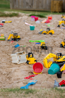 A children's sand pit play pit full of plastic buckets, spades and yellow toy diggers and excavators