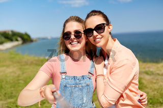 teenage girls or friends taking selfie in summer